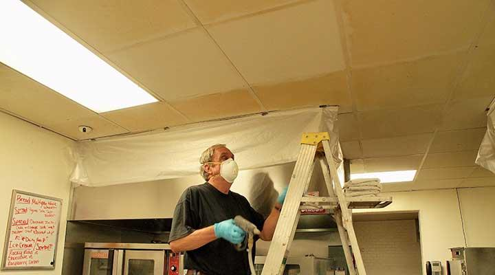 Guy cleaning ceiling tile